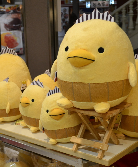 "Figure 8.  ""Bari-san"" yuru-kyara stuffed ""animals"" for sale. Bari-san is associated with Imabari City in Ehime Prefecture, famous for its chicken products. Photograph by author, 2013."