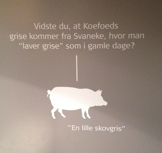 """Figure 4. Toilet door poster: """"Did you know that Koefoed's pigs come from Svaneke where they """"make pigs"""" as in the old days? --- """"a small forest pig"""" (photographed by Karrebæk)"""