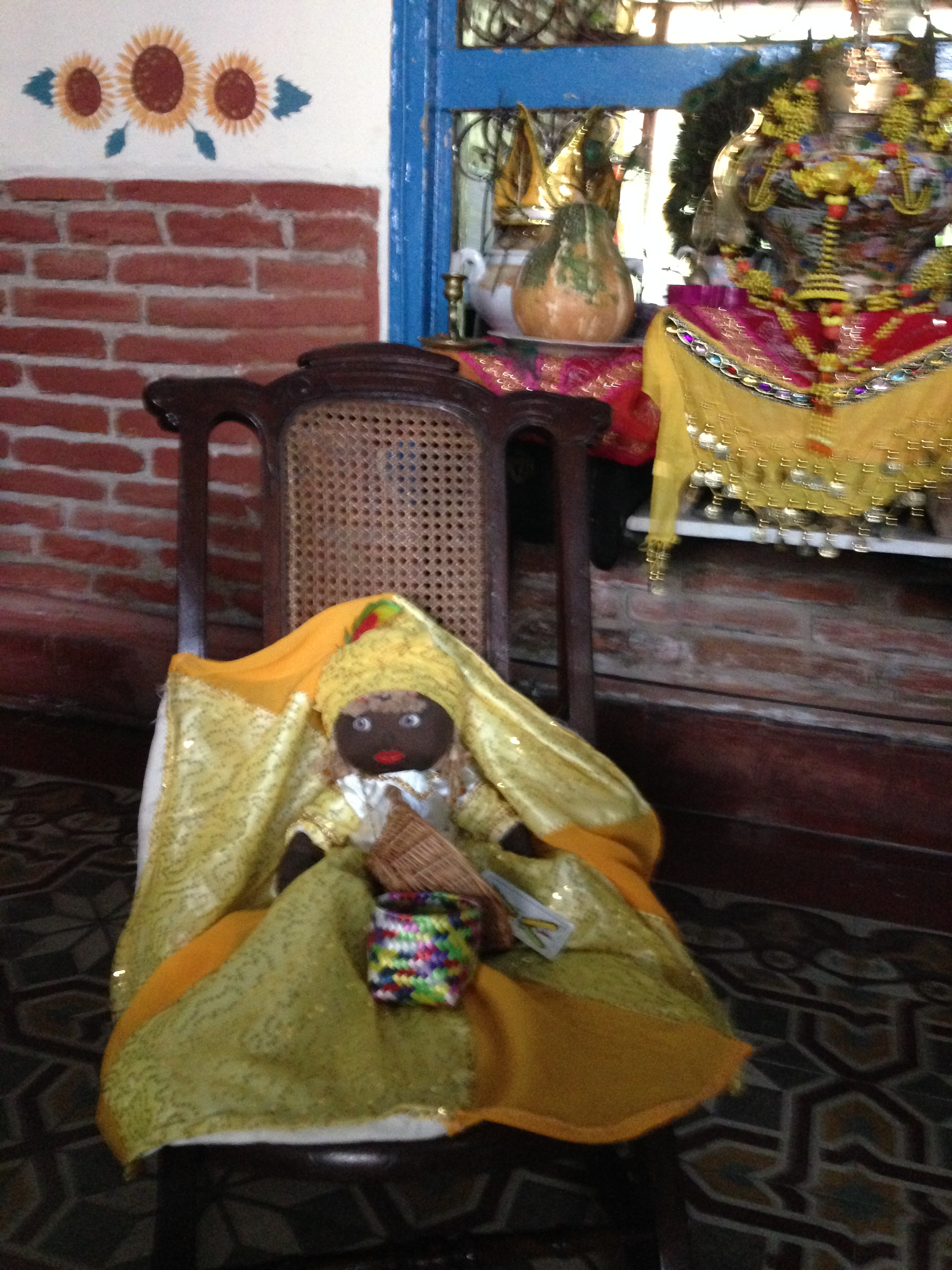 Figure 4. A spiritual doll representing the oricha Ochún (and the Virgin of Caridad del Cobre) occupies a prominent position on a rocking chair in the front room of a religious practitioner's house, where it faces the front door. The shelf behind the doll holds an elaborately decorated porcelain vessel containing the consecrated embodiment of Ochún. Santiago de Cuba, July 2014. Photograph by author.