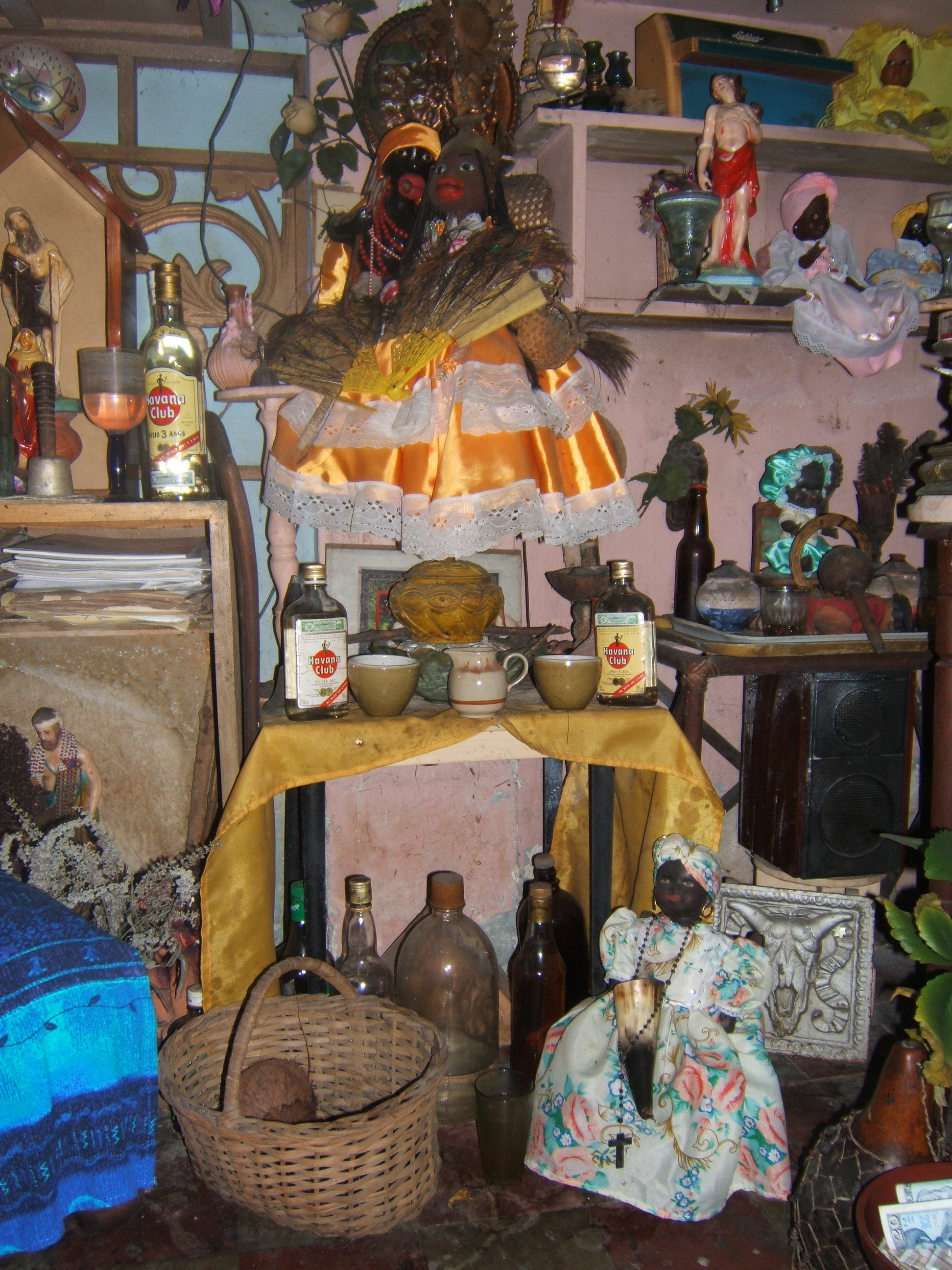 Figure 9. A close-up of Pedro's altar focused on a pair of cloth dolls adorned to represent the orichas Changó and Ochún, with closed vessels and rum offerings arrayed below them. On the floor, a plastic doll in a floral-print dress and head-wrap holds an mpaka or Palo object made of a horn. Santiago de Cuba, August 2008. Photograph by author.
