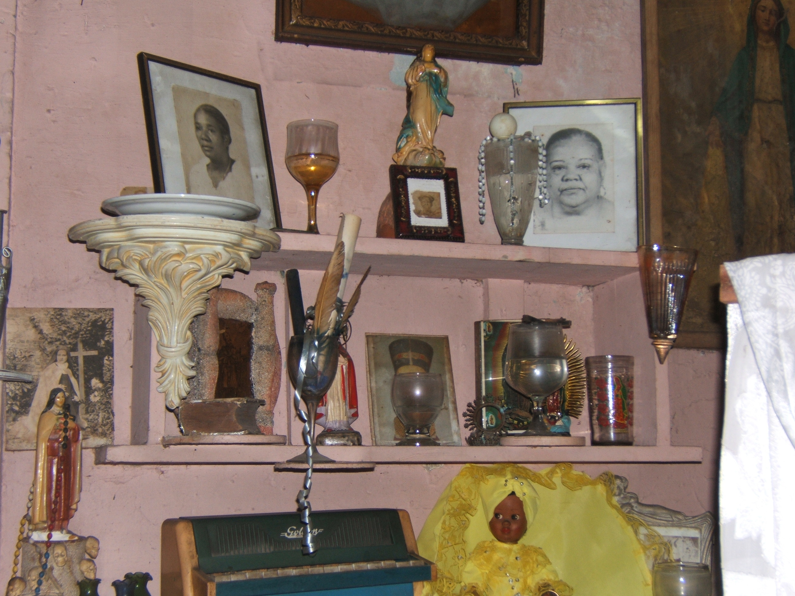 Figure 10. A close-up of Pedro's altar focused on two high shelves holding photographic portraits of deceased relatives, among other objects. Santiago de Cuba, August 2008. Photograph by author.