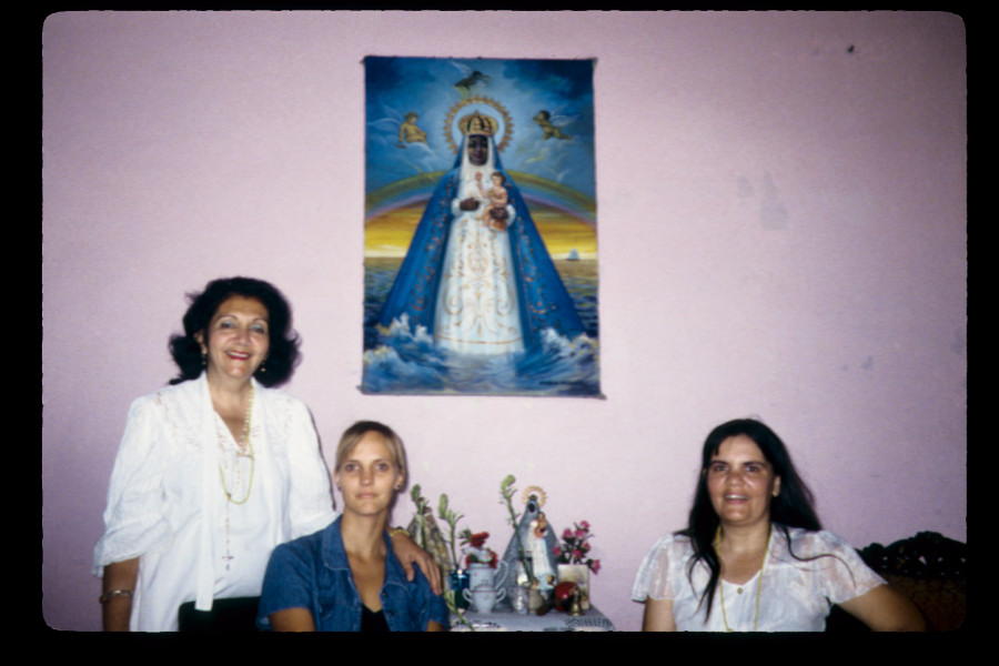 """Figure 13. Snapshot of Mirta, the author, and Mirta's daughter before Mirta's bóveda and painting of her spiritual """"mother,"""" the Virgin of Regla (corresponding to the oricha Yemayá), Santiago de Cuba, May 2000."""
