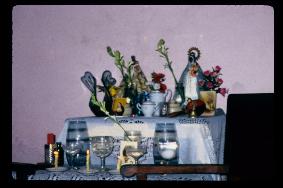 Figure 12. Mirta's bóveda or central Spiritist altar in her living room, holding offerings of lilies, goblets of water, and lit candles, Santiago de Cuba, May 2000.