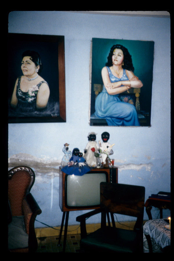 Figure 14. Mirta's muertos africanos or African spirits, posed as a family atop a large television set, below oil paintings of Mirta's mother and Mirta on the wall in her living room, Santiago de Cuba, May 2000.