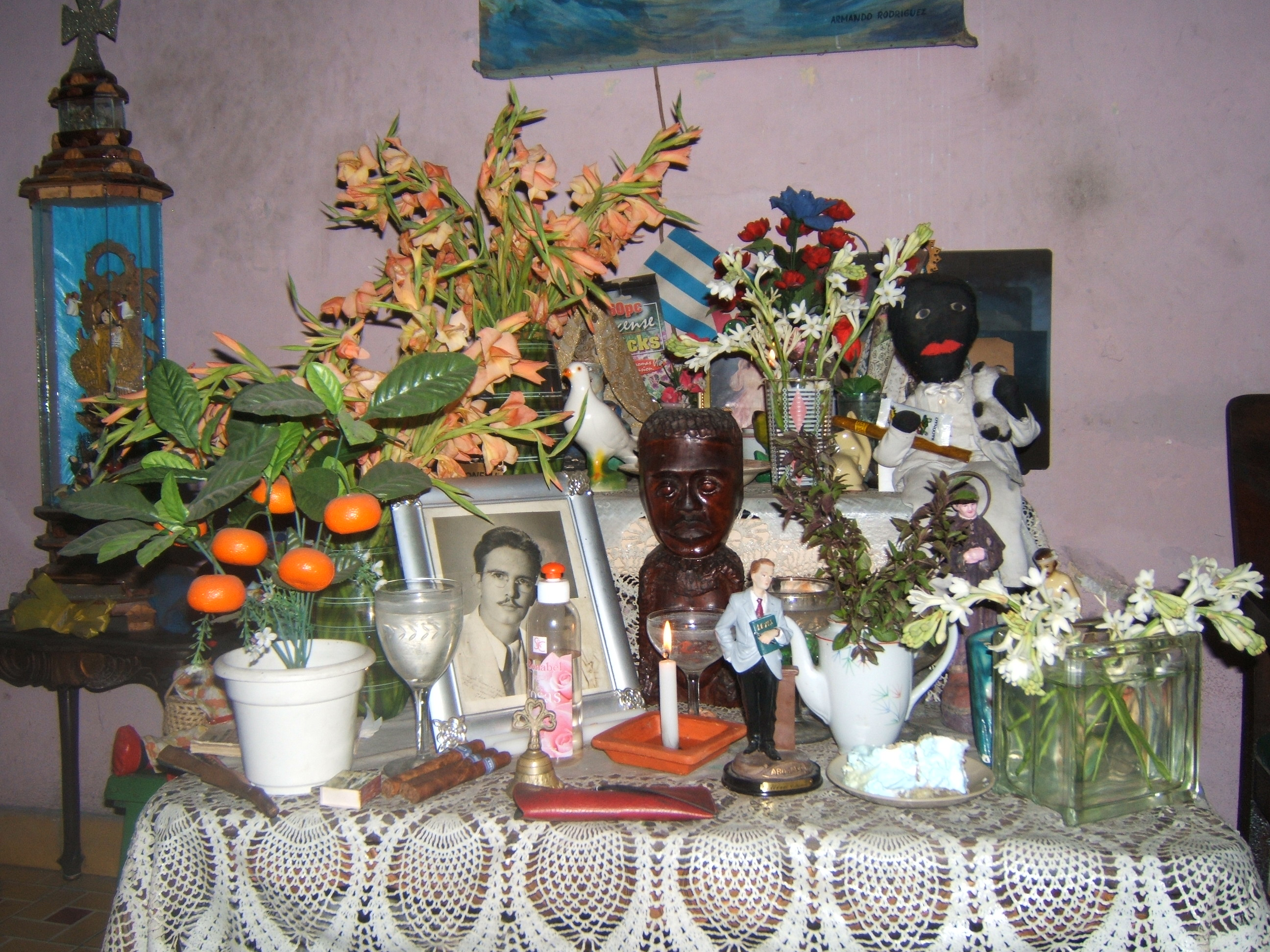 Figure 17. Mirta's bóveda prepared for a spiritual ceremony with lit candle, perfume squirt bottle, flowers, cigars, a serving of cake, and a packet of incense sticks, Santiago de Cuba, August 2008. Photograph by author.