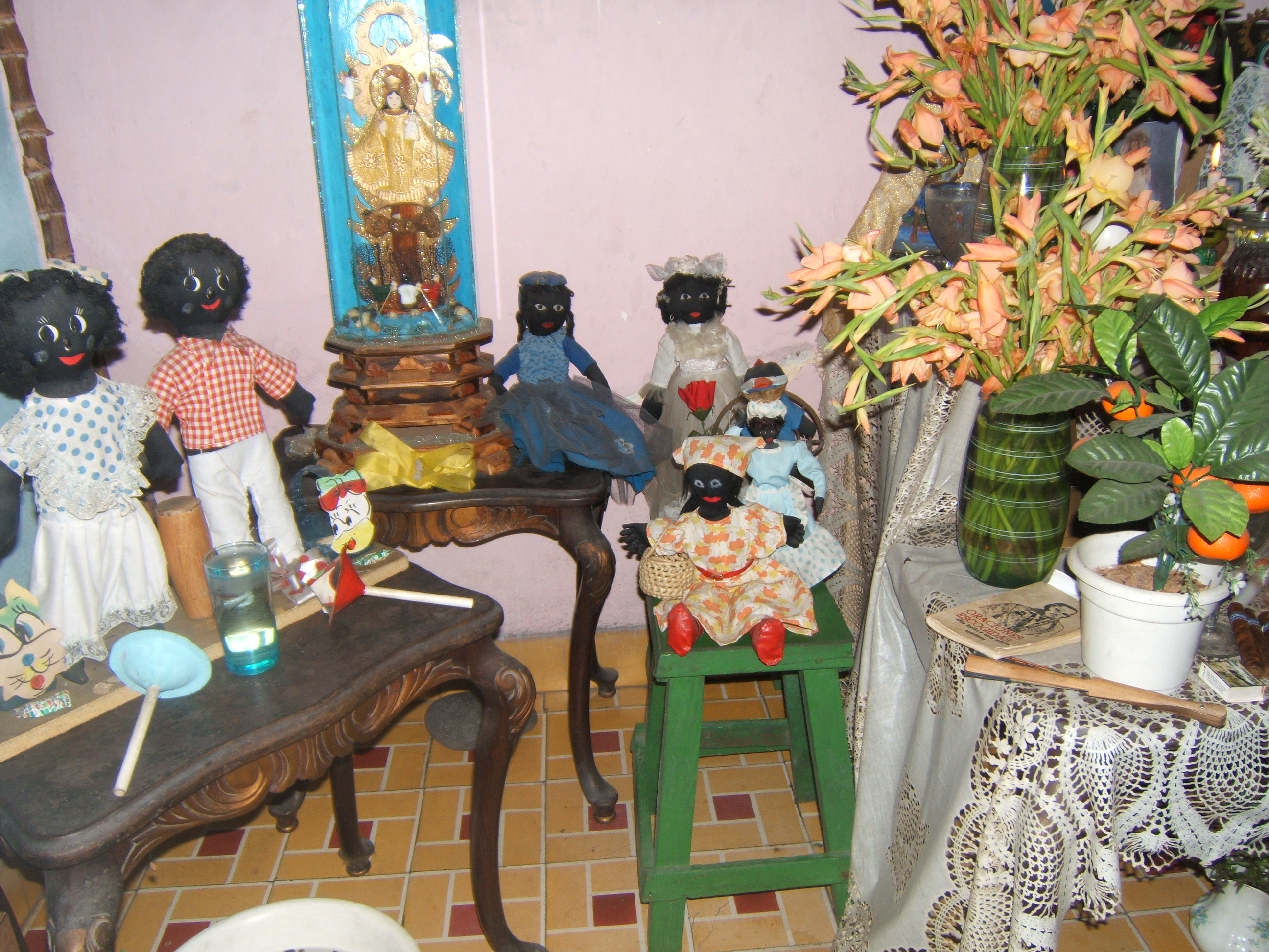 Figure 18. Side tables next to Mirta's bóveda hold dolls representing the Ibeyi or twin orichas (far left), an encased statuette of the Virgin of Caridad del Cobre against a blue background, and dolls representing African spirits, in a family grouping, Santiago de Cuba, August 2008. Photograph by author.